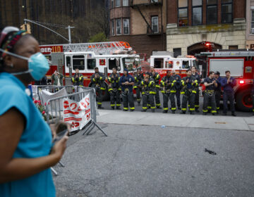 FDNY firefighters gather to applaud medical workers as attending physician Mollie Williams, left, wears personal protective equipment due to COVID-19 concerns outside Brooklyn Hospital Center, Tuesday, April 14, 2020, in New York. (AP Photo/John Minchillo)