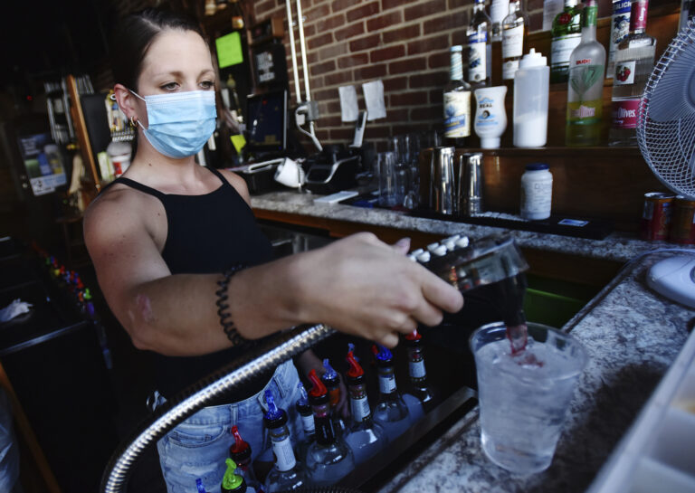 Bartender Kelsey Drozda makes a drink behind the bar at the Riverside Cafe in Wilkes-Barre, Pa., Wednesday, July 15, 2020.(Sean McKeag/The Citizens' Voice via AP)