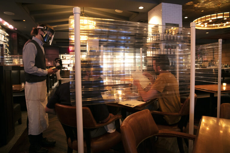 In this June 22, 2020, file photo, wearing a face shield, server Brandon Fricke, left, takes orders from dine-in customers surrounded by protective dividers at Water Grill seafood restaurant in Los Angeles. (AP Photo/Jae C. Hong)