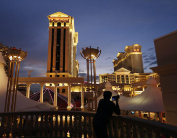 In this Jan. 12, 2015, file photo, a man takes pictures of Caesars Palace hotel and casino in Las Vegas. (AP Photo/John Locher)