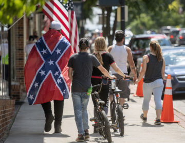 A young man wears a Confederate flag while walking with friends in Marion, VA Friday afternoon. (AP Photo/Andre Teague, Bristol Herald Courier)