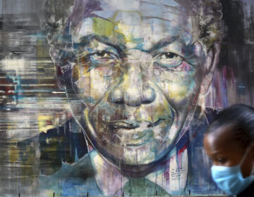 A masked woman walks past a mural of former President  Nelson Mandela in Cape Town, South Africa, Saturday July 18, 2020 as the country celebrates International Mandela Day. (AP Photo/Nardus Engelbrecht)