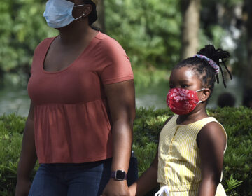 A child and her mother wear face masks while walking through a park