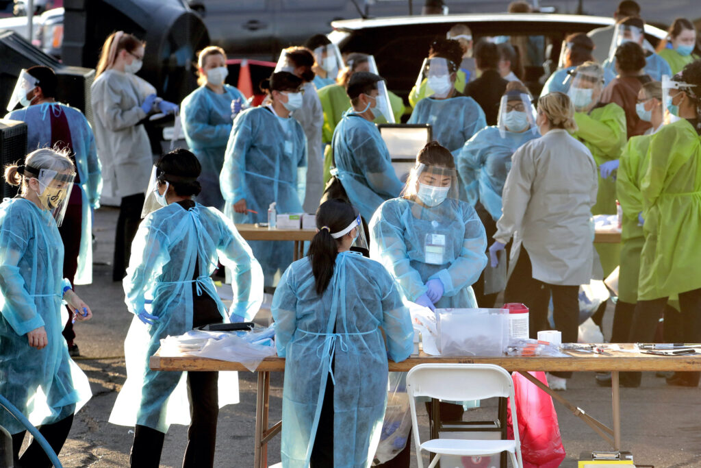 Medical personnel prepare to test hundreds of people lined up in vehicles