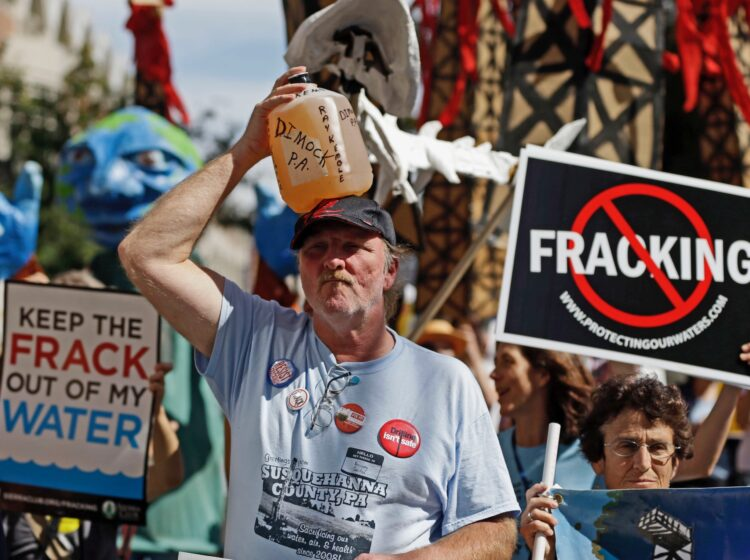 In this Sept. 20, 2012, file photo, Ray Kemble, of Dimock, Pa., holds a jug of his well water on his head while marching with demonstrators against hydraulic fracturing outside a Marcellus Shale industry conference in Philadelphia. (AP Photo/Matt Rourke, File)