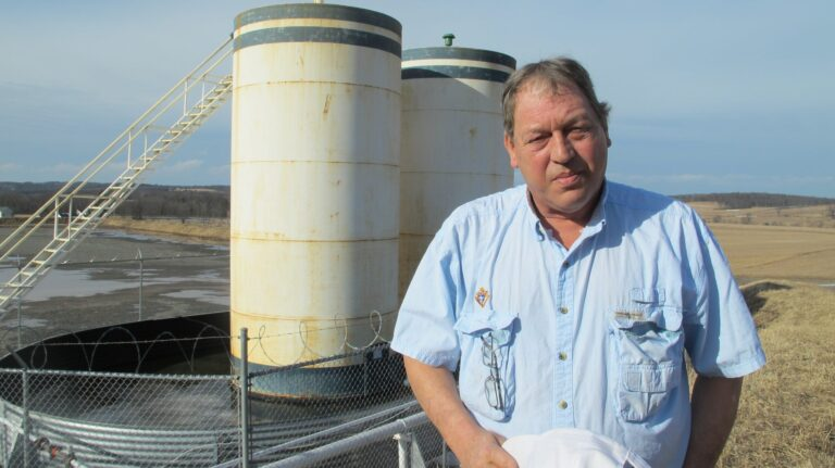 Jim Barrett stands next to a wellpad on his farm in Bradford County. He says Chesapeake Energy, which drilled four natural gas wells on his land, is cheating him out of royalty money. He is part of a class-action lawsuit against the company, which is separate from a case involving Chesapeake that's being pursued by the state Attorney General. (Marie Cusick/StateImpact Pennsylvania)