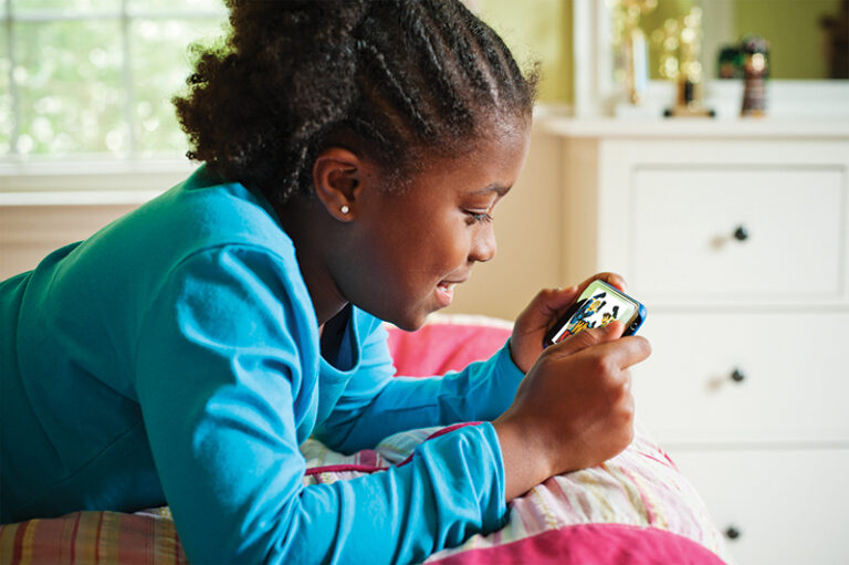 A young girl watching an education video on her phone while she lies in bed