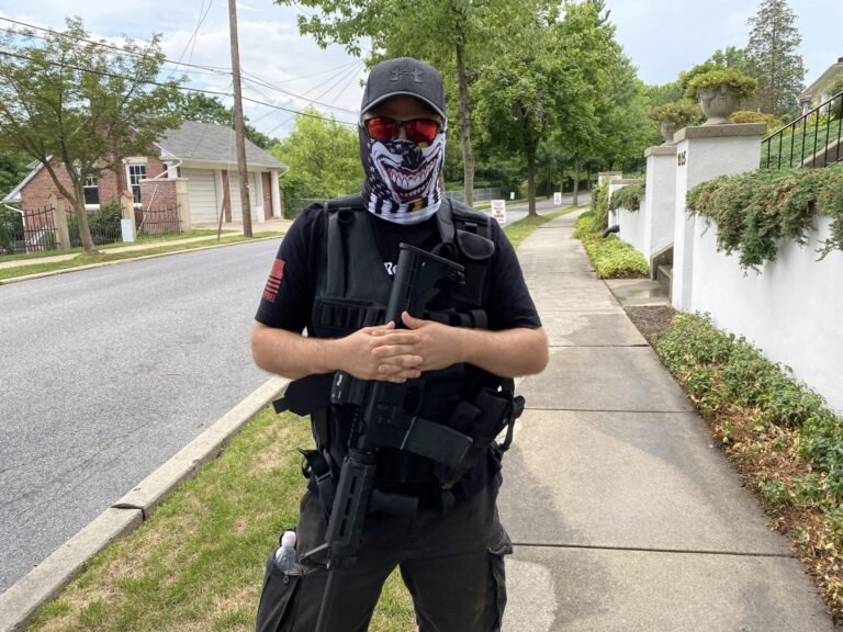 A man dressed in all black wore a tactical vest and carried an AR-15-style rifle