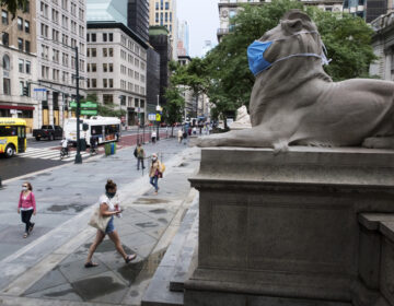 A face mask covers the mouth and nose of one of the iconic lion statues in front of the New York Public Library Main Branch on Wednesday, July 1, 2020, in New York, amid the coronavirus pandemic. (Ted Shaffrey/AP)