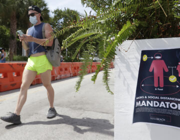 A pedestrian in a mask passes a sign urging people to practice social distancing, on Saturday in Miami Beach, Fla. Just as residents flocked outside to enjoy the Fourth of July, states such as Florida were reporting skyrocketing numbers of confirmed coronavirus cases. (Wilfredo Lee/AP Photo)