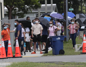People wait in line outside of a COVID-19 testing site in Florida.