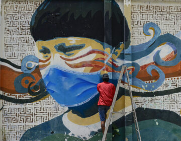 A street artist spray paints a protective face mask over an old mural featuring a Venezuelan Indigenous man