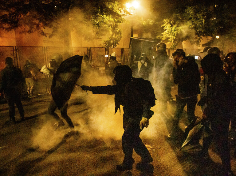Protesters walk through chemical irritants deployed by federal agents in Portland, Ore. The inspector general of the Justice Department says he is investigating federal officers' roles in responding to protests in Portland and Washington, D.C. (Noah Berger/AP Photo)