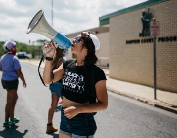 A protester with Black Lives Matter Harrisburg takes part in a protest outside Dauphin County Prison on June 30, 2020. Inmates inside the facility could be heard banging on the windows and holding up signs pleading for help. (Kate Landis/PA Post)