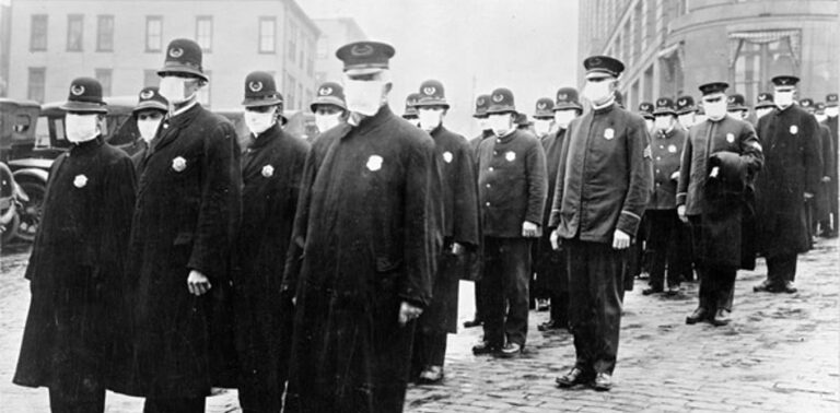 Policemen in Seattle, Washington, wearing masks made by the Red Cross, during the influenza pandemic, December 1918. (National Archives)