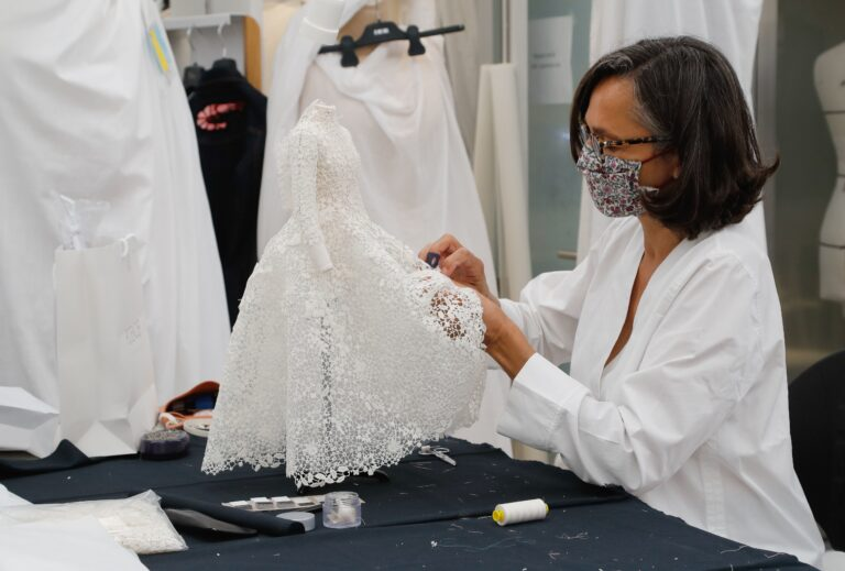 An employee sews a miniature dress in Dior's sewing workshop in Paris on July 4. This year Dior created a miniature collection for its haute couture show and presented it as a film. (Francois Guillot/AFP via Getty Images)