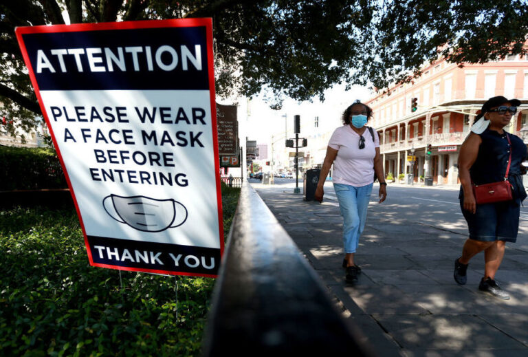 Visitors walk past face mask signs along Decatur Street