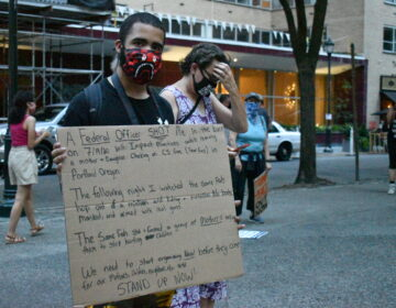 Jordan Johnson holds a sign detailing a recent incident with what he says were federal police in Portland, Oregon. (Brett Sholtis/WITF)
