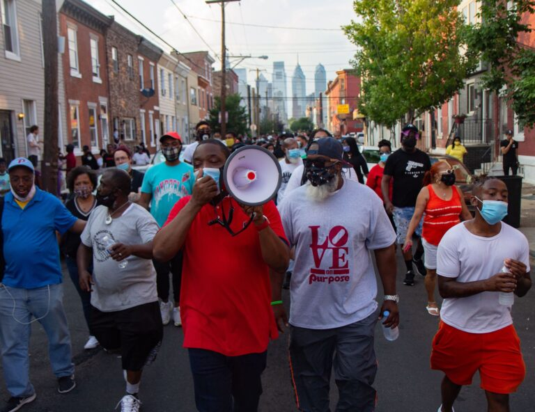 "Councilmember Kenyatta Johnson led a protest chant, ""Don't shoot, I want to live"" as residents fed up with gun violence marched through South Philadelphia. (Kimberly Paynter/WHYY)"