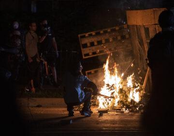 A protester in Kenosha lights some debris on fire on Aug. 26, 2020. (Angela Major/WPR)