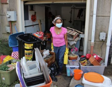 Yvette Palmer, 70, carries belongings out of the flooded first floor of her Eastwick home. (Emma Lee/WHYY)