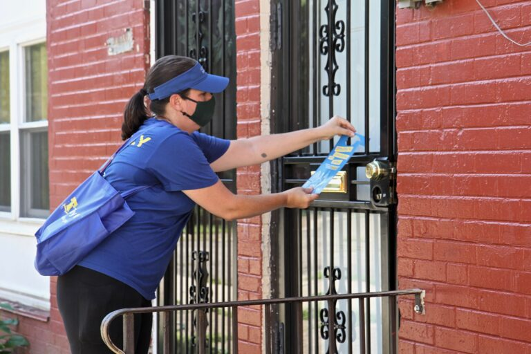 Stephanie Reid, executive director of Philly Counts, places a doorhanger about the census on a resident's house. (Ximena Conde/WHYY)