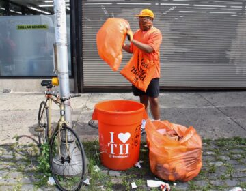 Matthew George changes the bag at his I Love Thy Hood can outside the Dollar General on Chelten Avenue.