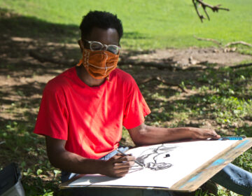 Nick Moncy, a young Black man, draws outside in a West Philadelphia park while wearing a mask