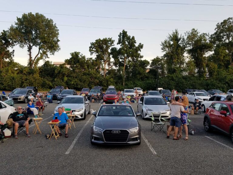 People and cars gathered at a parking lot turned into a drive-in during the coronavirus pandemic