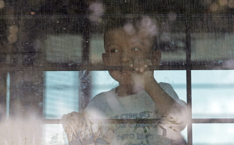 An immigrant child looks out from a U.S. Border Patrol bus as protesters block the street outside the U.S. Border Patrol Central Processing Center Saturday, June 23, 2018, in McAllen, Texas. (AP Photo/David J. Phillip)