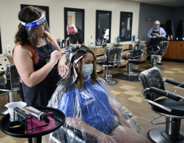 Salon Vizions stylist Michaela Slayton colors Paulette Fultz hair with Personal Protection Equipment on and Fultz wears a mask with a disposable gown on in Johnstown, Pa, Friday, June 5, 2020. (Todd Berkey/The Tribune-Democrat via AP)