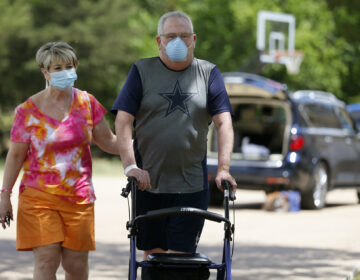 Terri Donelson, left, and her husband, Stephen, walk up their driveway to see friends and family awaiting him at his home in Midlothian, Texas on Friday, June 19, 2020, after his 90-day stay in the Zale Hospital on the UT Southwestern Campus. (AP Photo/Tony Gutierrez)