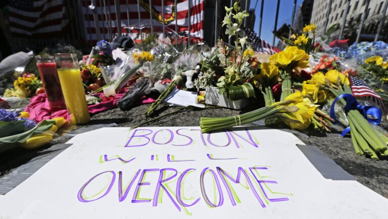 In this April 17, 2013 photograph, flowers and signs adorn a barrier, two days after two explosions killed three and injured hundreds, at Boylston Street near the of finish line of the Boston Marathon at a makeshift memorial for victims and survivors of the bombing. (AP Photo/Charles Krupa)