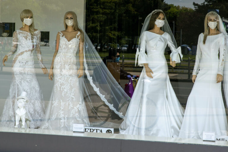 A cyclist wearing a coronavirus protective mask is reflected in a wedding dresses store window where mannequins also wear masks, in Zagreb, Croatia, Thursday, April 23, 2020. The store is closed because of Covid-19 lockdown. (AP Photo/Darko Bandic)