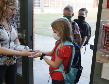 In this Aug. 5, 2020, file photo, wearing masks to prevent the spread of COVID19, elementary school students use hand sanitizer before entering school for classes in Godley, Texas. (AP Photo/LM Otero)