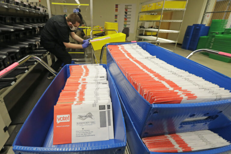Vote-by-mail ballots are shown in sorting trays, Wednesday, Aug. 5, 2020, at the King County Elections headquarters in Renton, Wash., south of Seattle. (AP Photo/Ted S. Warren)