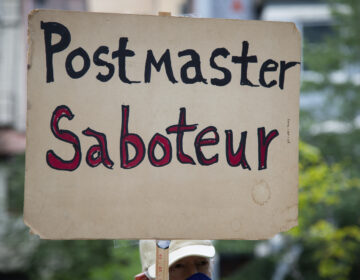 A protester holding a sign waits to march to the residence of Postmaster GeneralLouisDeJoy - a major Republican donor who President Trump recently nominated to run the United States Postal Service (USPS) despite concerns about conflicts of interest and lack of experience - to demonstrate against Dejoy's changes to the USPS, which many say are acts of sabotage to increase Trump's chances in a mostly vote-by-mail election in Washington, D.C., on August 15, 2020, amid the coronavirus pandemic. DeJoy reportedly has invested tens of millions of dollars in direct USPS competitors, and recently he has enacted many changes at the USPS that postal worker unions and election experts say will make the election difficult or impossible to carry out effectively. (Graeme Sloan/Sipa USA)(Sipa via AP Images)
