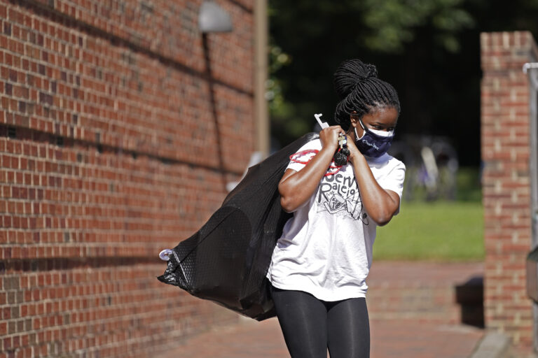 Oyeronke Popoola, a 17-year-old freshman from Raleigh, carries some of her belongings as she and other students leave campus following a cluster of COVID-19 cases at The University of North Carolina in Chapel Hill, N.C., Tuesday, Aug. 18, 2020. (AP Photo/Gerry Broome)