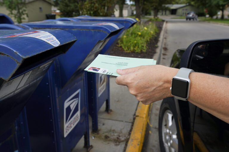 A person drops into a mail box applications for mail-in ballots