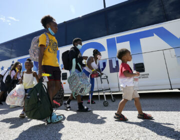 Evacuees walk to board buses Tuesday, Aug. 25, 2020, in Galveston, Texas. The evacuees are being taken to Austin, Texas, as Hurricane Laura heads toward the Gulf Coast. (AP Photo/David J. Phillip)