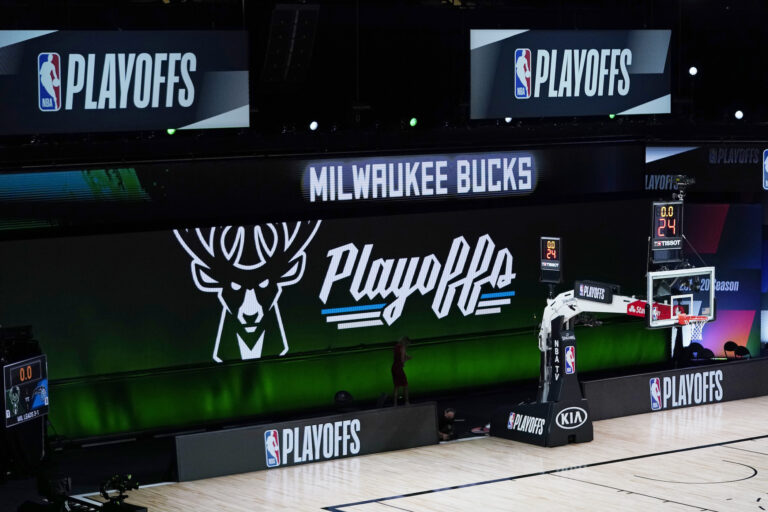 Milwaukee Bucks signage is displayed on screens beside an empty court before the scheduled start of an NBA basketball first round playoff game between the Milwaukee Bucks and the Orlando Magic, Wednesday, Aug. 26, 2020, in Lake Buena Vista, Fla. (AP Photo/Ashley Landis, Pool)