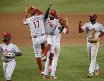 Philadelphia Phillies' Andrew McCutchen, left, Rhys Hoskins (17), Roman Quinn, third from left, and Didi Gregorius, right, celebrate after a baseball game against the Washington Nationals, Wednesday, Aug. 26, 2020, in Washington. The Phillies won 3-2. (AP Photo/Nick Wass)
