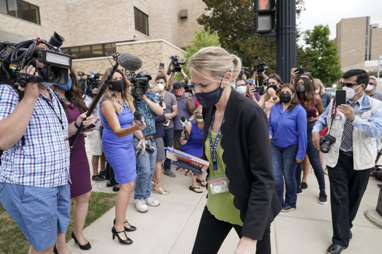 Kasey Morgan, a public information officer for the Lake County Court, walks away from reporters outside the Lake County courthouse following the extradition hearing for Kyle Rittenhouse Friday, Aug. 28, 2020, in Waukegan, Ill. (AP Photo/Morry Gash)