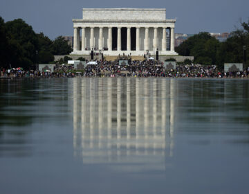 The Lincoln Memorial is reflected in the water as people gather to attend the March on Washington, Friday Aug. 28, 2020, in Washington, on the 57th anniversary of the Rev. Martin Luther King Jr.'s