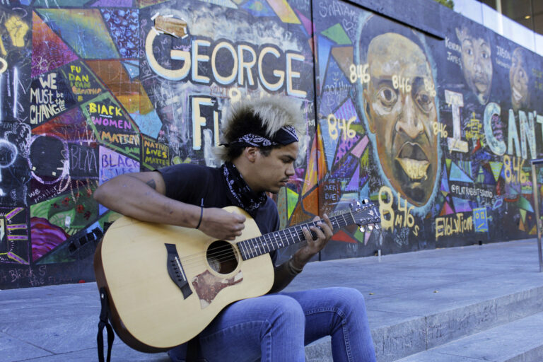 Shane Braswell, who has participated in Black Lives Matter protests this summer, plays guitar in front of a mural covering the entrance to an Apple store, Aug. 27, 2020 in Portland, Ore. Braswell said President Donald Trump's portrayal of Portland as a violent city overcome by mobs of protesters is inaccurate and grossly exaggerated.
