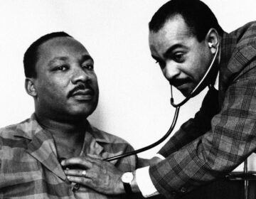 Dr. Walter Lomax, a Philadelphia physician, tending to Dr. Martin Luther King, Jr. in his hotel room bed in Philadelphia, Feb. 10, 1968. (AP Photo)