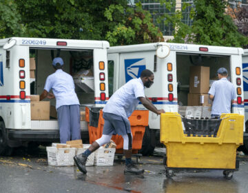 Letter carriers load mail trucks for deliveries at a U.S. Postal Service facility
