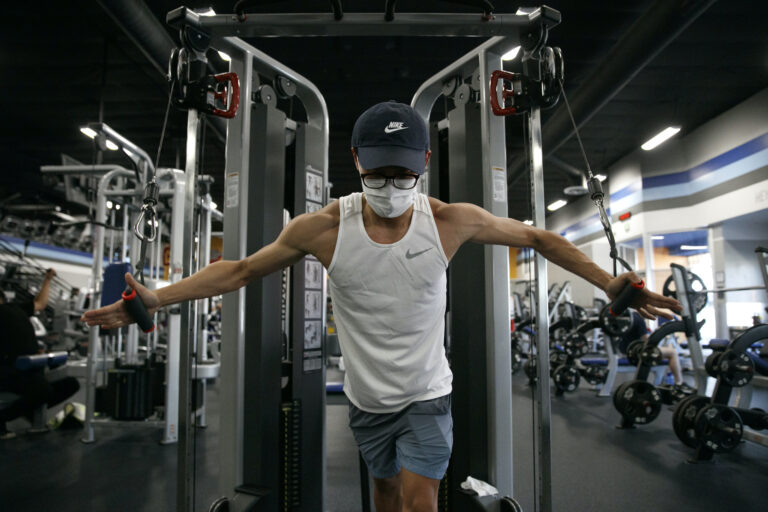 Benji Xiang, 32, wears a mask while working out at a gym