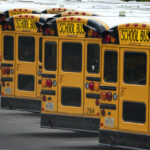 Fairfax County Public School buses are lined up at a maintenance facility