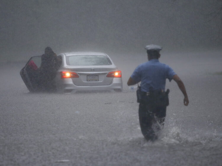 A Philadelphia police officer rushes to help a stranded motorist during Tropical Storm Isaias